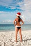 圣诞老人帽子的妇女在海滩 图库摄影