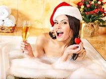圣诞老人帽子的妇女在浴放松。 免版税库存照片