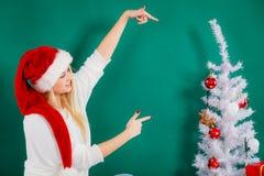 圣诞老人帽子的妇女坐沙发放松 库存图片