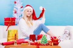 圣诞老人帽子的妇女坐沙发放松 库存照片