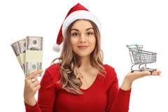 戴圣诞老人帽子的妇女拿着小购物车和金钱Bu 免版税库存图片
