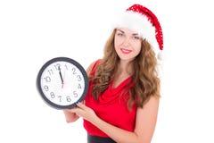 圣诞老人帽子的妇女有在白色隔绝的时钟的 免版税库存图片