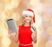 圣诞老人帽子的妇女有片剂个人计算机和信用卡的 免版税库存图片
