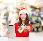 圣诞老人帽子的妇女有片剂个人计算机和信用卡的 库存照片