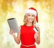 圣诞老人帽子的妇女有片剂个人计算机和信用卡的 图库摄影