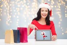 圣诞老人帽子的妇女有片剂个人计算机和购物袋的 免版税库存照片