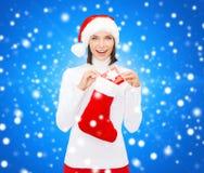 圣诞老人帽子的妇女有礼物盒和长袜的 库存照片