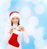 圣诞老人帽子的妇女有礼物盒和长袜的 免版税图库摄影