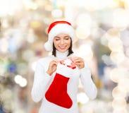圣诞老人帽子的妇女有礼物盒和长袜的 免版税库存图片
