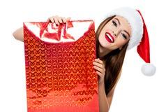 圣诞老人帽子的妇女有购物袋的 免版税库存图片