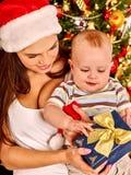戴圣诞老人帽子的妈妈抱着婴孩下 免版税库存图片