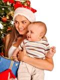 戴圣诞老人帽子的妈妈抱着婴孩下 免版税库存照片