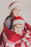 圣诞老人帽子的孩子在圣诞树附近,等待假日 图库摄影
