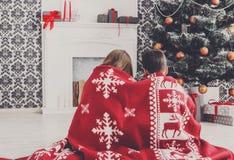 圣诞老人帽子的孩子在圣诞树附近,等待假日 库存图片