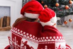 圣诞老人帽子的孩子在圣诞树附近,等待假日 免版税库存图片