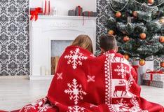 圣诞老人帽子的孩子在圣诞树附近,等待假日 免版税库存照片