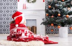 圣诞老人帽子的孩子在圣诞树附近,等待假日 库存照片