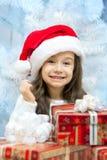 圣诞老人帽子的孩子有礼物盒的。 免版税库存照片