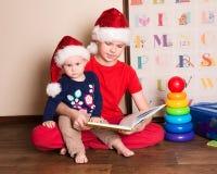 圣诞老人帽子的孩子读圣诞节书的 哥哥rea 库存图片