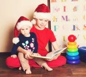 圣诞老人帽子的孩子读圣诞节书的 哥哥rea 免版税库存图片