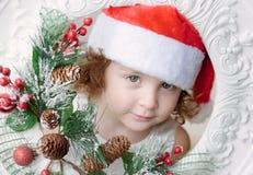 圣诞老人帽子的小卷曲女孩有圣诞节花圈的 库存图片