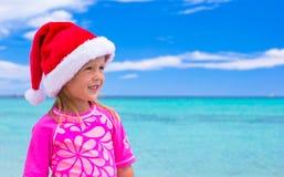 戴圣诞老人帽子的小可爱的女孩在热带 库存图片
