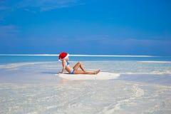 圣诞老人帽子的小女孩在海滩在期间 免版税库存图片