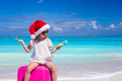 圣诞老人帽子的小女孩坐有地图的一个大手提箱在手上 库存照片