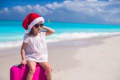 圣诞老人帽子的小女孩带着手提箱暑假 免版税库存照片
