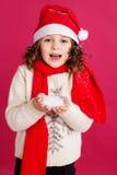 圣诞老人帽子的小女孩拿着假雪 库存图片