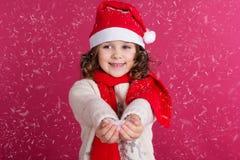 圣诞老人帽子的小女孩拿着假雪 库存照片