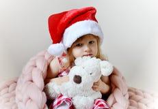 圣诞老人帽子的小女孩有玩具狗等待的圣诞节的 免版税库存图片