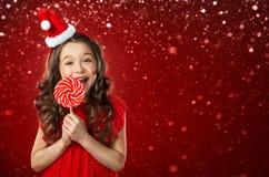 圣诞老人帽子的小女孩用在红色背景的糖果 背景圣诞节关闭红色时间 免版税库存图片