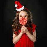 圣诞老人帽子的小女孩用糖果,被隔绝的黑暗的背景 库存照片