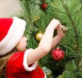 圣诞老人帽子的小女孩装饰圣诞树的 免版税库存照片