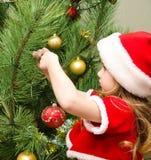 圣诞老人帽子的小女孩装饰圣诞树的 免版税库存图片