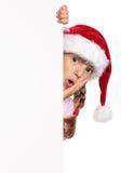 圣诞老人帽子的小女孩 免版税库存图片