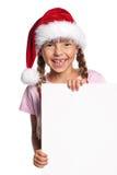 圣诞老人帽子的小女孩 图库摄影