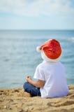 圣诞老人帽子的小男孩坐沙子海洋 库存图片