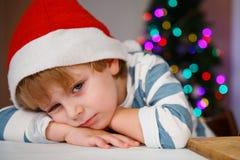 圣诞老人帽子的小男孩有圣诞树和光的 图库摄影