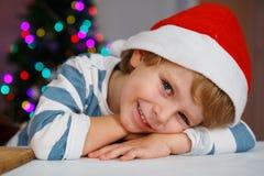 圣诞老人帽子的小男孩有圣诞树和光的 免版税图库摄影