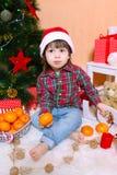 圣诞老人帽子的小男孩用蜜桔在圣诞树附近坐 免版税库存照片