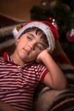 圣诞老人帽子的小逗人喜爱的男孩为礼物作梦 免版税库存照片