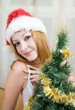 圣诞老人帽子的少妇在圣诞树附近 库存图片