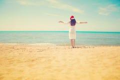 圣诞老人帽子的少妇在热带海滩 圣诞节连接了特别是空的行业互联网膝上型计算机办公室照片与结构树usb假期有关 圣诞节海滩假期穿圣诞老人帽子和比基尼泳装的旅行妇女 库存图片