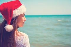 圣诞老人帽子的少妇在热带海滩 圣诞节连接了特别是空的行业互联网膝上型计算机办公室照片与结构树usb假期有关 圣诞节海滩假期穿圣诞老人帽子和比基尼泳装的旅行妇女 库存照片