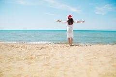 圣诞老人帽子的少妇在热带海滩 圣诞节连接了特别是空的行业互联网膝上型计算机办公室照片与结构树usb假期有关 圣诞节海滩假期穿圣诞老人帽子和比基尼泳装的旅行妇女 免版税库存照片