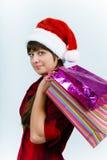 圣诞老人帽子的少妇有假日购物的 库存照片