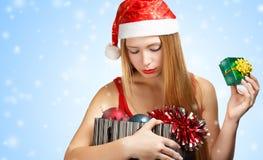 圣诞老人帽子的少妇有圣诞节属性和一点美国兵的 免版税库存图片