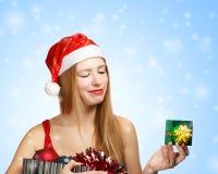 圣诞老人帽子的少妇有圣诞节属性和一点美国兵的 免版税库存照片